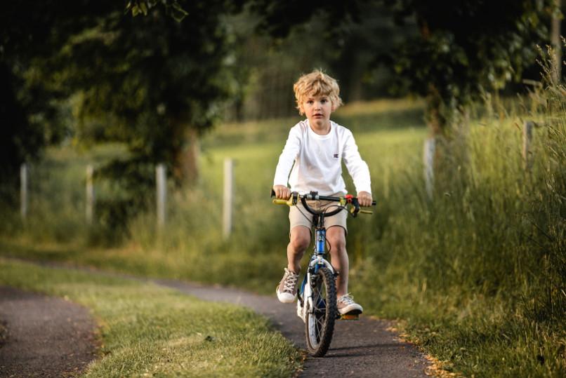 Photo d'un petit enfant sur un vélo bleu