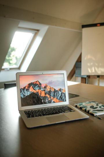 Photo d'un bureau avec un ordinateur portable et un cahier