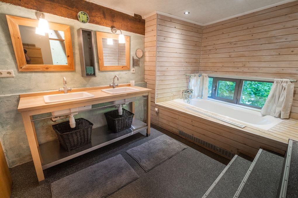 Salle de bain avec baignoire donnant sur le jardin