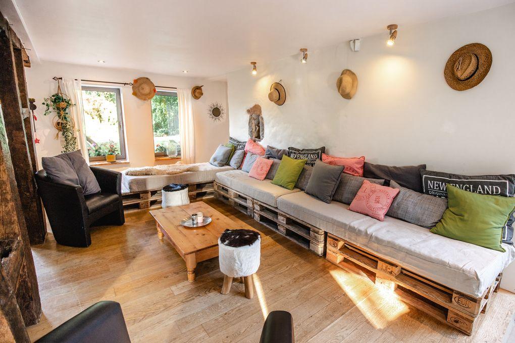 Salon avec canapé en palettes et nombreux coussins