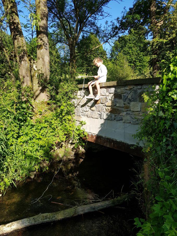 garçonnet pêchant du haut d'un petit pont de pierre