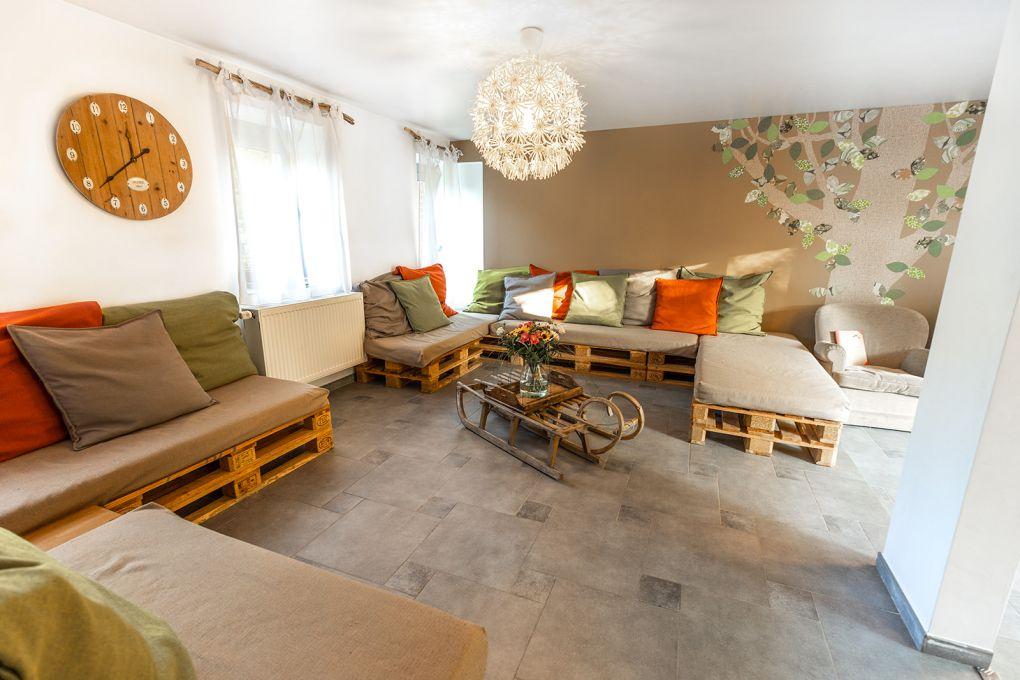 Salon avec canapé en palette et nombreux coussins